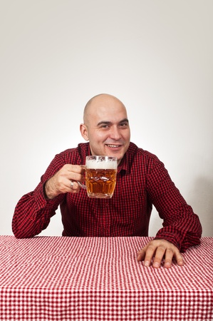 Bald beer drinker sitting in the bar with a glass of cold lager on the table. photo