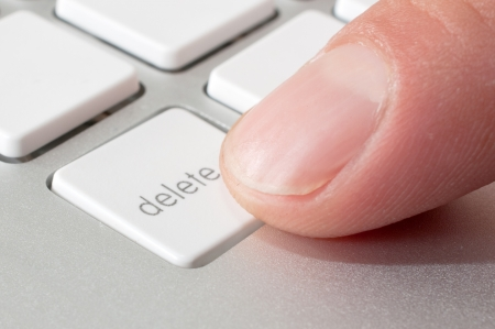 Finger is pressing delete key of a modern stylish aluminium white computer keyboard photo