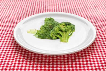 broccolli: Fresh raw broccoli on a white plate Red and white checkered kitchen tablecloth in background  Stock Photo