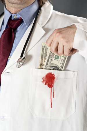 Bribe in medicine - doctor taking money into his pocket  Bribe and corruption in health and medicine industry concept  photo