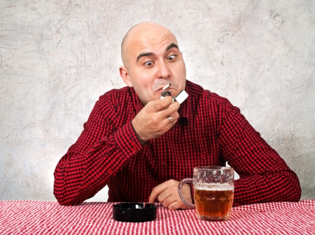 drinker: Young adult beer drinker lighting up a cigarette in the bar