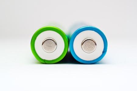 aa: AA bateeries. Green and blue AA batteries close up.