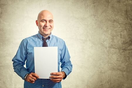 Businessman holding blank white paper as a document, cv or contract. photo