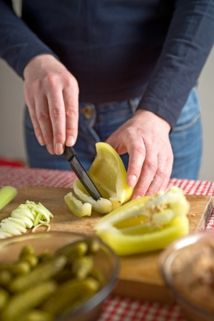 Female hands cutting bell pepper on a wowod chopboard with black ceramic knife. photo