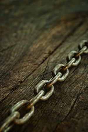 Rusty chain on weatherd wood background. Stock Photo - 19397660