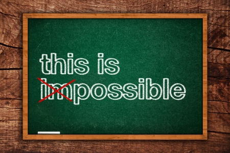 This is possible message hand written on a green chalkboard, motivational postivie thinking concept of possible and impossible photo