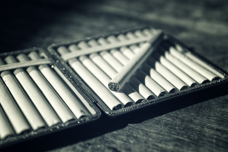 cigarette smoke: Cigarettes in cigarette case on wood table. Day light with dark shadows.