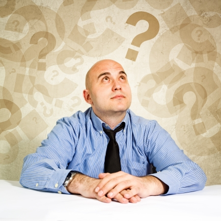 Businessman thinking and questioning, loooking at question marks around his head.