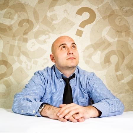 questionnement: Homme d'affaires penser et de questionnement, loooking � des points d'interrogation autour de sa t�te.