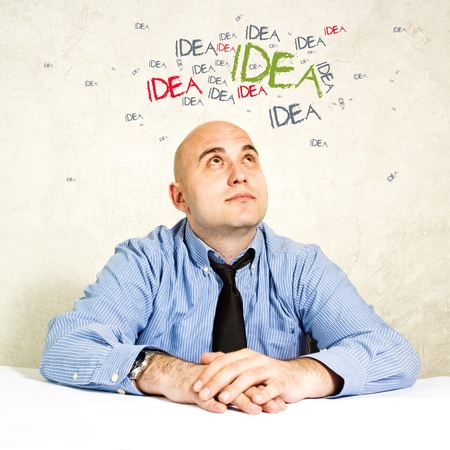 Business idea  Businessman brainstorming and looking up, ideas swarming around his head  photo