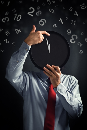 Businessman with black clock in front of his head, deadline concept. Not enough time to finish the job. photo