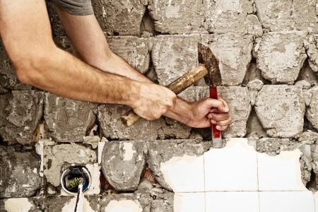 azulejos ceramicos: Hombre que rompe baldosas en el ba�o, redecoraci�n casa Foto de archivo