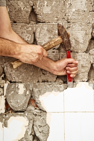 redecoration: Man breaking ceramic tiles in the bathroom, home redecoration. Stock Photo