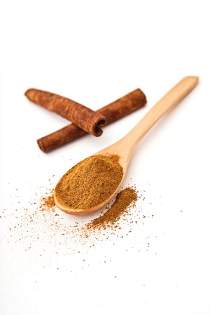 milled: Milled cinnamon on wooden spoon, cinnamon sticks in background Stock Photo