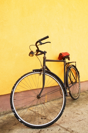 Old vintage black bicycle leaning on the wall. photo