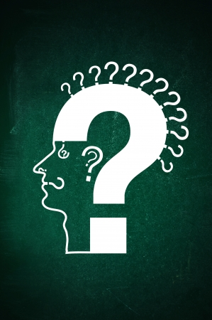 Human head made of question marks on a green chalkboard. Qusetion everything concept: thoughts; look; smell; hear; speak.