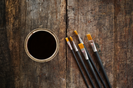 Paint brushes and paint can on old wood background. photo