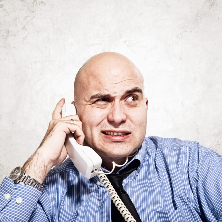 Frustrated businessman in messy situation talking on the phone. photo