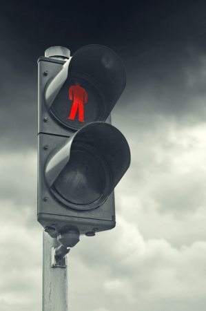 Red traffic light for pedestrians against gray cloudy sky. photo