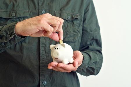Man putting coin into white piggy coin bank. photo