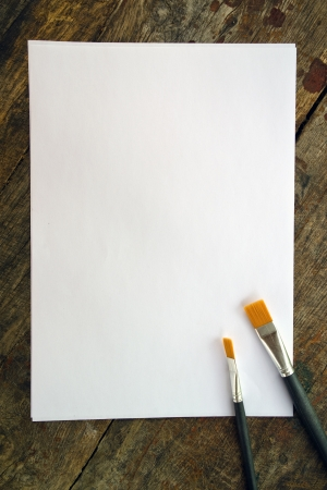 paint tool: Paint brushes and blank white paper on old wood background.