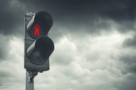 red traffic light: Red traffic light for pedestrians against gray cloudy sky.