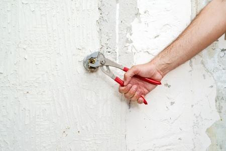 Hands screwing water valve. Housework. photo