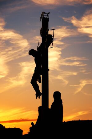 crucified: Crucifixion statue on Charles Bridge in Prague, Czech Republich. Image is taken against the light in the sunset.