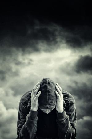 Man met problemen. Man in kap met handen op zijn hoofd. Drugsverslaafde concept.