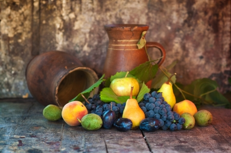 Old wooden table full of various fresh autumn fruit  apple, pear, grape, plum and peach  photo