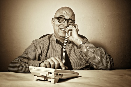 wheeler: Smiling businessman at office desk with telephone. Wheeler dealer or business crook. Stock Photo