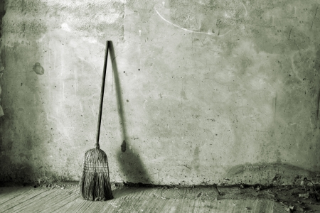 brushwood: Old obsolete broom or besom leaning on the gray wall Stock Photo