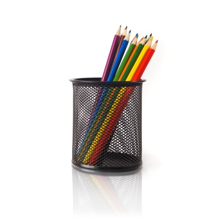 Wood color pencils in black metal pencil holder over a white background photo