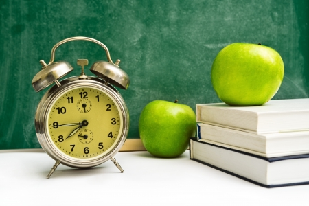back to school supplies: School time again  Clock, apples and books on teacher
