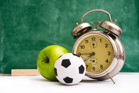 school time: School time again  Clock, small ball and apple on teacher Stock Photo