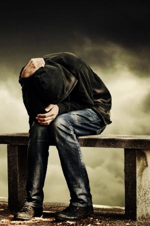 Man met problemen Mens in kap met de handen op zijn hoofd zitten op de betonnen bank drugverslaafde begrip