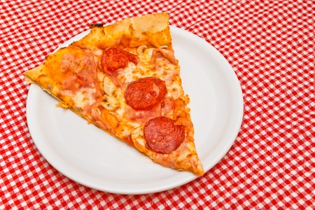Pizza slice on white plate served on kitchen table photo