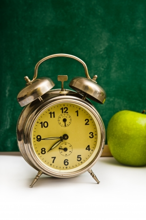 school time: School time again  Clock and apples on teacher Stock Photo