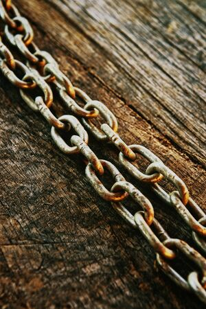 linkage: Rusty chain on weatherd wood background.