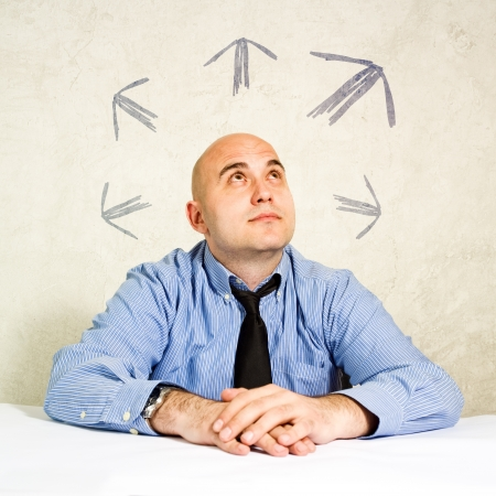 business decisions: Business choice or business making decisions  Businessman looking at arrows above him  Concept of choice, choosing between possible solutions