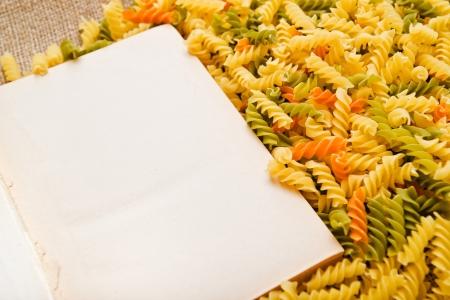 rotini: Italian fusilli o rotini y libro de recetas abierto con p�ginas en blanco