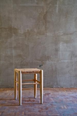alienation: Vintage old wooden chair in grungy interior. Loneliness, estrangement, alienation concept.