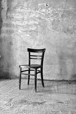 Vintage old black wooden chair in grungy interior. Loneliness, estrangement, alienation concept. photo
