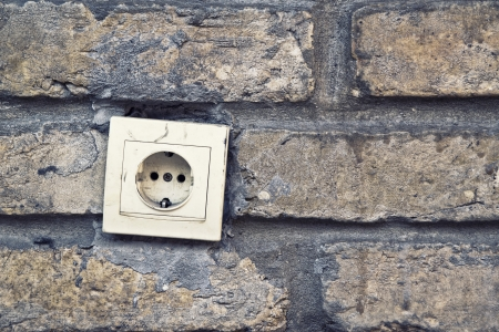 Old plastic electric plug connector, ac outlet, on brick wall. photo