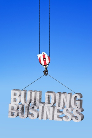 deployment: Building business in construction industry. Construction crane lifting concrete letters.