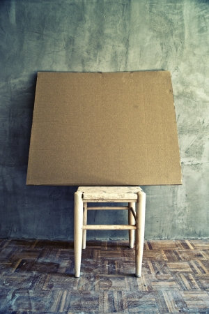 alienation: Old vintage chair and empty cardboard in grungy interior. Loneliness, estrangement, alienation concept.