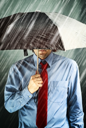 hard times: Businessman with black umbrella protecting himself from the storm. Financial problem, economic crisis, hard times concept.