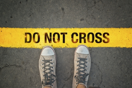 Man in sneakers standing at the yellow line with Do Not cross message Banco de Imagens