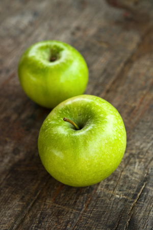 Green apples on old wood table, obsolete wooden texture. photo