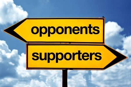 opponents: Opponents or supporters opposite signs. Two opposite road signs against blue sky background.